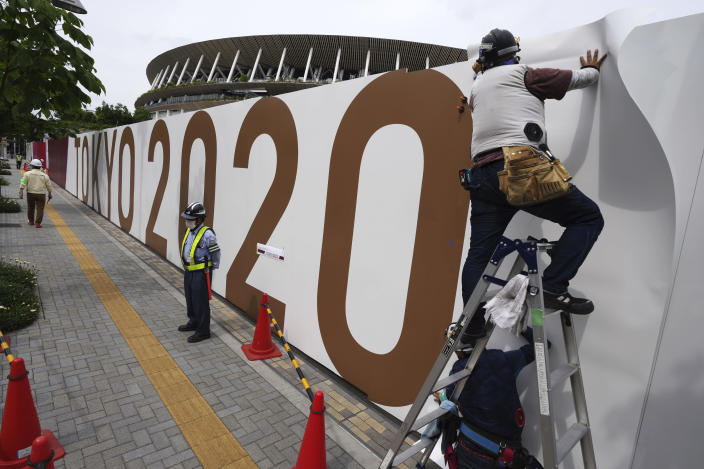 FILE - In this June 2, 2021, file photo, workers paste the overlay on the wall of the National Stadium, in Tokyo. The Tokyo Olympics are not looking like much fun: Not for athletes. Not for fans. And not for the Japanese public, who are caught between concerns about the coronavirus at a time when few are vaccinated on one side and politicians and the International Olympic Committee who are pressing ahead on the other. (AP Photo/Eugene Hoshiko, File)