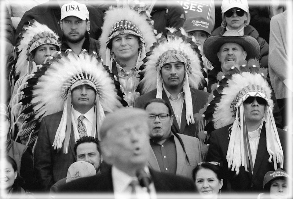 A group of Native Americans wearing traditional headdresses listen as President Donald Trump speaks during a campaign rally for Republican U.S. Senate candidate Matt Rosendale in Belgrade, Montana in 2018. (Photo: Carlos Barria/Reuters; digitally enhanced by Yahoo News)