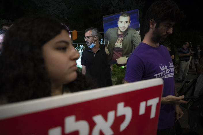 """Protesters hold pictures and chant slogans during a demonstration against violence near the house of Public Security Minister Omer Barlev in the central Israeli town of Kokhav Ya'ir, Saturday, Sept. 25, 2021. Arab citizens of Israel are seeking to raise awareness about the spiraling rate of violent crime in their communities under the hashtag """"Arab lives matter,"""" but unlike a similar campaign in the United States, they are calling for more policing, not less. (AP Photo/Sebastian Scheiner)"""