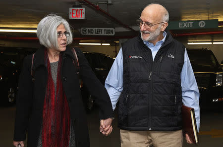 Alan and Judy Gross walk through a parking garage after arriving for a news conference in Washington