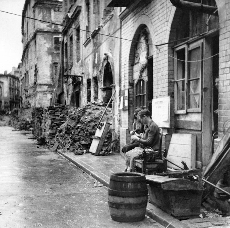 A picture showing Poles sitting in a rubble-strewn street at the end of World War II