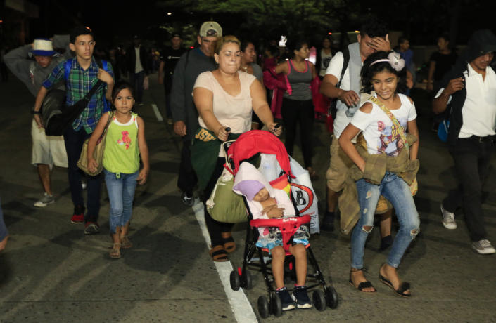 Migrants walk along a highway in hopes of reaching the distant United States, in San Pedro Sula, Honduras, before sunrise Wednesday, Jan. 15, 2020. Hundreds of Honduran migrants started walking and hitching rides Wednesday from the city of San Pedro Sula, in a bid to form the kind of migrant caravan that reached the U.S. border in 2018. (AP Photo/Delmer Martinez)