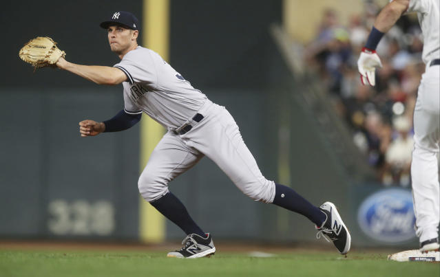 New York Yankees first baseman Greg Bird has to reach wide of the base on a wide throw from pitcher J.A. Haps who fielded an infield hit by Minnesota Twins' Jake Cave in the second inning of a baseball game Monday, Sept. 10, 2018, in Minneapolis. (AP Photo/Jim Mone)