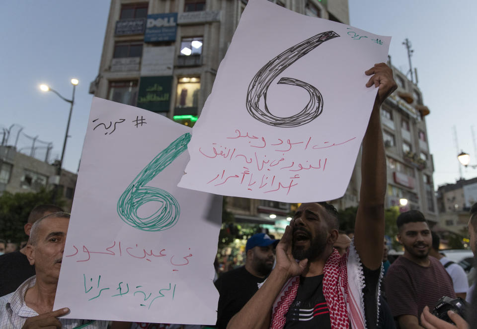 """Protesters chant anti Israel slogans and carry placards that read """"six lions found the light at the end of the tunnel, freedom for our prisoners,"""" during a rally supporting Palestinian prisoners in Israeli jails, in the West Bank city of Ramallah, Wednesday, Sept. 8, 2021. Pressure built around Israel's prison system Wednesday after fires broke out at several facilities and the government searched for six Palestinian escapees who have been on the run since they tunneled out two days earlier. (AP Photo/Nasser Nasser)"""