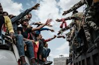 People on a bus reach out to the returning rebels in Mekele