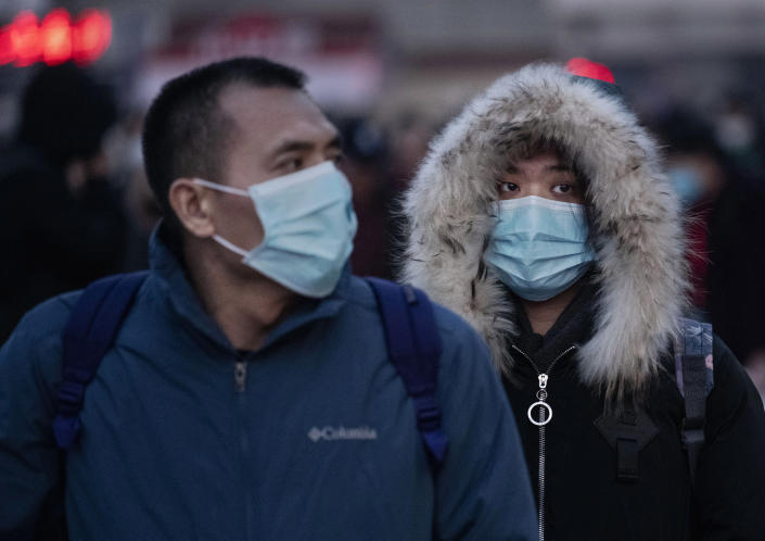 Chinese travellers wear protective masks as they arrive to board trains at Beijing railway station as fears grow over the coronavirus. (Getty)