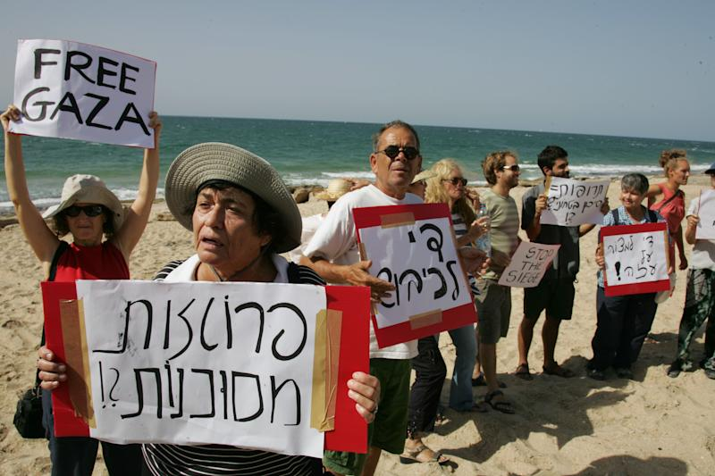 """Israeli left-wing activists protest at the beach near the port of Ashdod, in the Mediterranean sea, southern Israel, Tuesday, Sept. 28, 2010. Israeli naval forces on Tuesday intercepted a catamaran carrying nine Jewish activists as they sailed toward the Gaza Strip. Israeli forces encountered no resistance taking control of the sailboat and escorted to the Israeli port of Ashdod, the military said. The incident occurred four months after a deadly Israeli raid on an international flotilla, in which nine Turkish activists were killed in clashes with naval commandos. Banners in Hebrew read, from left to right: """"Prostheses are dangerous?!"""", """"End the occupation"""", """"Drugs = security hazard?!"""", and """"Stop the siege of Gaza"""". (AP Photo/Yehuda Lahyani) ** ISRAEL OUT **"""