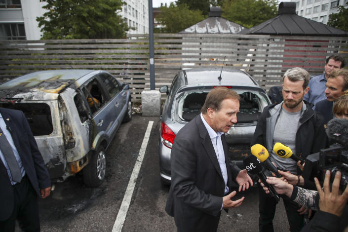 """Swedish Prime Minister Stefan Lofven foreground, talks to journalists, after cars were set on fire, at Frolunda Square, in Gothenburg, Sweden, Tuesday, Aug. 14, 2018. Masked youth torched dozens of cars overnight in Sweden and threw rocks at police, prompting an angry response from the prime minister, who spoke of an """"extremely organized"""" night of vandalism. (Henrik Brunnsgard/TT News Agency via AP)"""