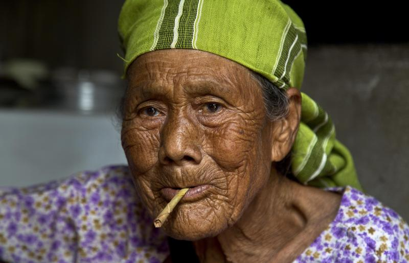 In this Saturday, May 11, 2019, photo, Bum Nongrum, 91, smokes a beedi, tobacco rolled in an indigenously available leaf, at her house in Nongpoh, in the northeastern Indian state of Meghalaya. Nongrum says she does not understand the concept behind exercising her franchise but has always cast her vote. Combined, India's tribals total more than 100 million people, scattered among hundreds of communities. For many tribal women, elections have become little more than another chore. (AP Photo/Anupam Nath)