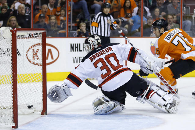 New Jersey Devils' Martin Brodeur, left, reaches to cover the puck after it became stuck in the netting as Philadelphia Flyers' Chris VandeVelde skates in during the second period of an NHL hockey game, Tuesday, March 11, 2014, in Philadelphia. (AP Photo/Matt Slocum)