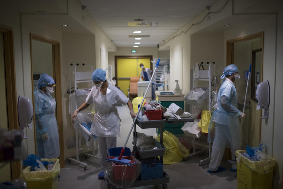 Medical workers wearing protective layers of plastic prepare to clean rooms in the hallway of a makeshift ICU at the La Timone hospital in Marseille, southern France, Thursday, Nov. 12, 2020. (AP Photo/Daniel Cole)