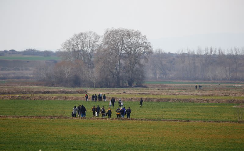 A group of migrants walk through the Turkish-Greek border in a village near the border city of Edirne