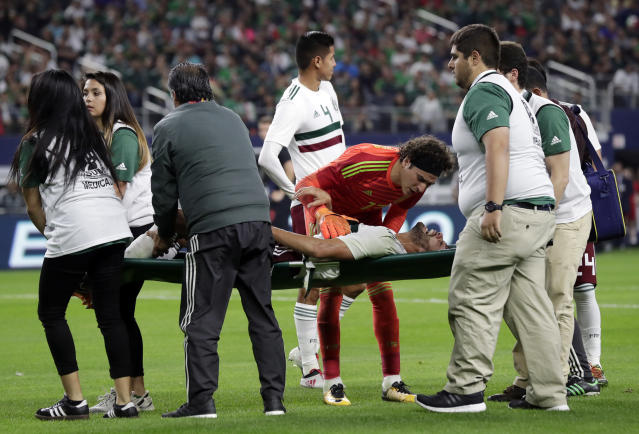 Mexico goalkeeper Guillermo Ochoa (13) talks to defender Nstor Araujo as he is carried off the field after suffering a leg injury in the first half of a friendly soccer match against Croatia in Arlington, Texas, Tuesday, March 25, 2018. (AP Photo/Tony Gutierrez)