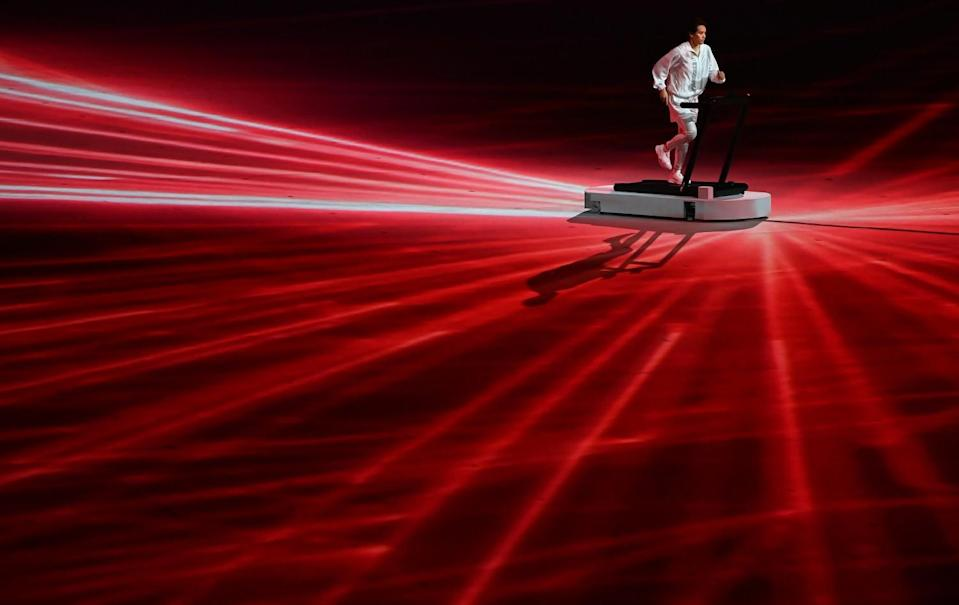 A man runs on a treadmill onstage surrounded by laser lights