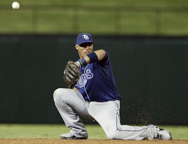Tampa Bay Rays' Yunel Escobar can't make the catch on a ball hit by Texas Rangers' Craig Gentry during the third inning of an American League wild-card tiebreaker baseball game Monday, Sept. 30, 2013, in Arlington, Texas. (AP Photo/Tony Gutierrez)