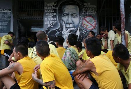 "Detainees sit next to a mural of Philippines President Rodrigo Duterte while authorities search through belongings for illegal contraband inside the Manila City Jail in metro Manila, Philippines October 16, 2017. The words on the mural read ""Steer away from illegal drugs to save your life and in turn, will save the country's"". REUTERS/Romeo Ranoco"