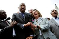FILE PHOTO: U.S. House Minority Leader Nancy Pelosi (D-CA) holds hands with Rep. John Lewis (D-GA) as they sing along with House Democrats after their sit-in over gun-control law on Capitol Hill in Washington