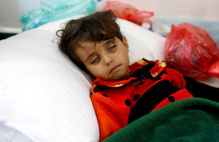 FILE PHOTO: Girl infected with cholera lies on the ground at a hospital in Sanaa