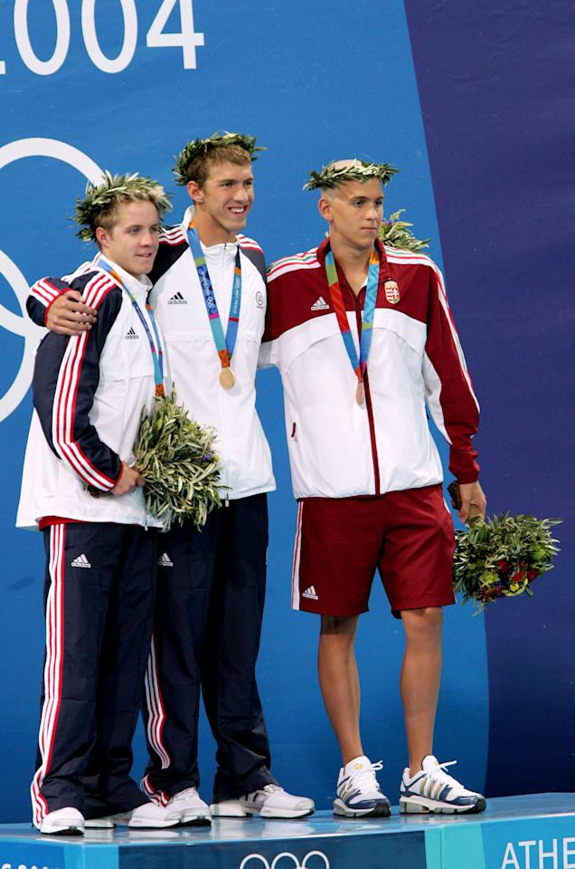 Michael Phelps of the United States wins the Olympic gold and sets a new world record in men's 400m Individual Medley in 4:08:26 before compatriot Erik Vendt (L) and Hungary's Laszlo Cseh (R) at the Olympic Aquatic Centre in Athens, Greece, August 14, 2004. (Photo by Chris Ivin/WireImage)