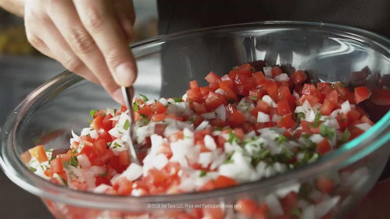Hand mixing a bowl of salsa.