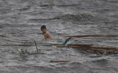A fisherman retrieves debris from his fishpen destroyed by strong winds brought by Typhoon Rammasun (locally named Glenda) as it hit the coastal town of Bacoor, Cavite southwest of Manila, July 16, 2014. REUTERS/Erik De Castro