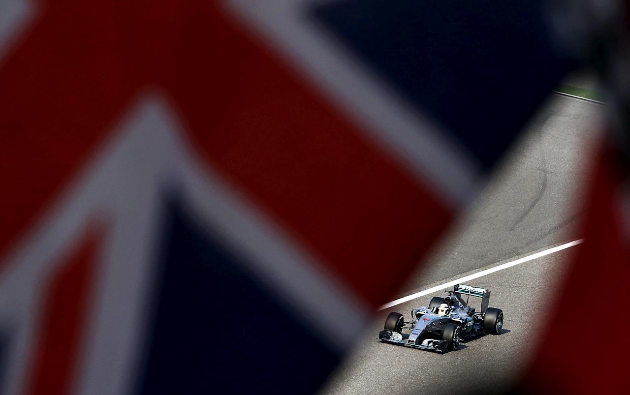 FILE PHOTO -  Mercedes Formula One driver Lewis Hamilton of Britain is seen behind British national flags in the last lap  of the Chinese F1 Grand Prix at the Shanghai International Circuit, April 12, 2015. REUTERS/Carlos Barria/File Photo