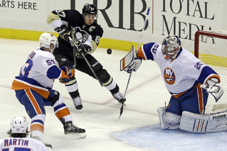 New York Islanders goalie Evgeni Nabokov (20) blocks a shot as Pittsburgh Penguins' Sidney Crosby, center, tries to bat the rebound in front of Casey Cizikas (53) during an NHL hockey game in Pittsburgh, Friday, Oct. 25, 2013. (AP Photo/Gene J. Puskar)