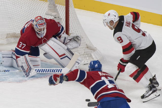 New Jersey Devils' Taylor Hall (9) moves in on Montreal Canadiens goaltender Keith Kinkaid as Canadiens' Brett Kulak defends during the first period of an NHL hockey game in Montreal, Saturday, Nov. 16, 2019. (Graham Hughes/The Canadian Press via AP)