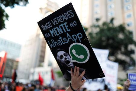 """A woman holds a sign with an image of presidential candidate Jair Bolsonaro that reads """"He lies in WhatsApp,"""" during a protest against Bolsonaro in Sao Paulo, Brazil, October 20, 2018. REUTERS/Nacho Doce"""