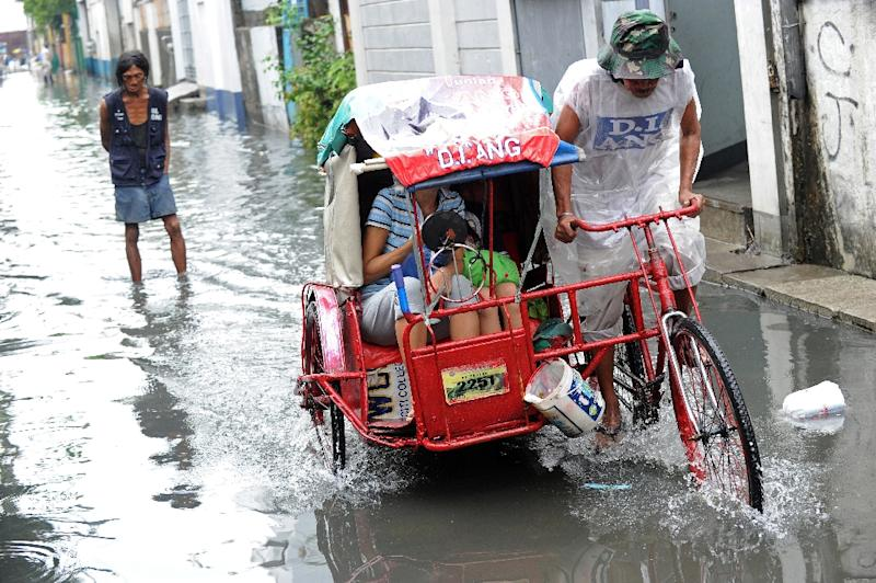 A rickshaw driver negotiates floodwaters in suburban Manila, on December 16, 2015 (AFP Photo/Jay Directo)