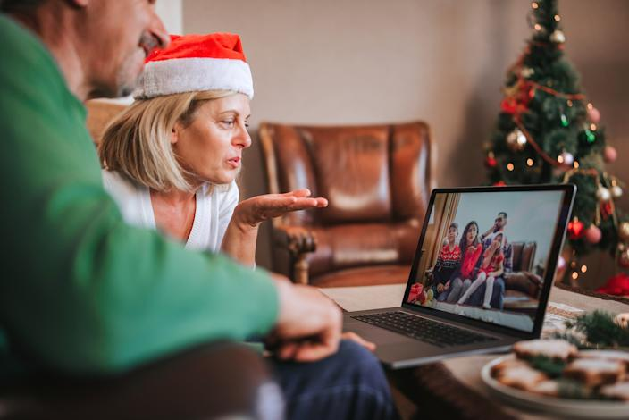 Video calls rather than texting can help alleviate feelings of isolation during the holidays. Image via Getty Images.