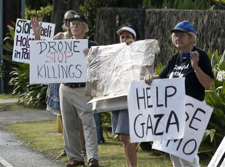 Protesters hold signs as the motorcade of U.S. President Barack Obama returns to Obama's vacation home in Kailua, Hawaii December 28, 2013. REUTERS/Kevin Lamarque