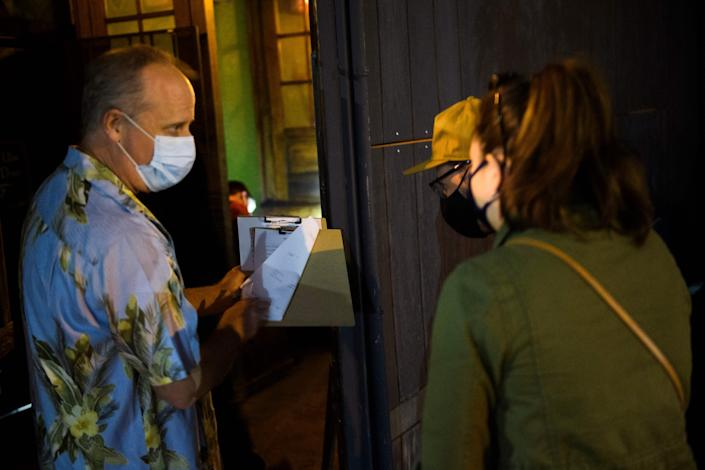 Co-owner Jonathan Katz talks to new members about a membership form outside Risky Business, that was once The Other Door but closed during the Covid-19 pandemic in the North Hollywood neighborhood of Los Angeles, California on May 21, 2021. - In order to go inside Risky Business, members must present their original vaccination card after being fully vaccinated, paying a small membership fee, signing a risk release form with penalties for lying, and waiting a full two weeks after competing their shots. While the policy is strict, once inside customers can enjoy an experience knowing that everyone else has been 100-percent vaccinated with an lively pre-pandemic atmosphere with people up close and personal - talking, hugging, playing pool and drinking without rules for masks or social distancing. (Photo by Patrick T. FALLON / AFP) (Photo by PATRICK T. FALLON/AFP via Getty Images)
