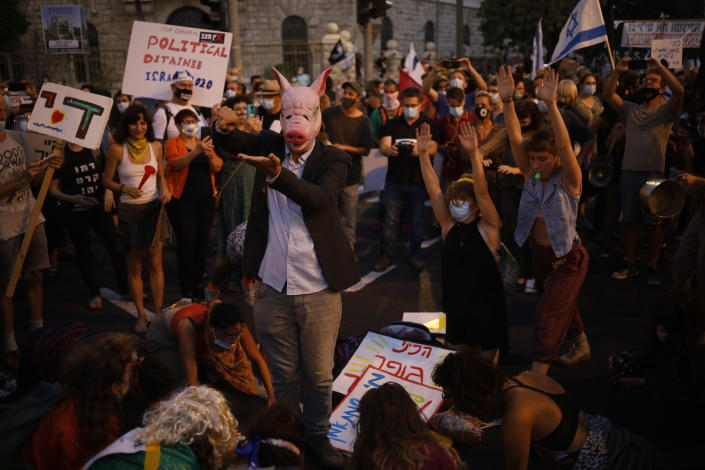 Protesters, defying orders to maintain social distancing requirements, chant slogans outside of the Prime Minister's residence in Jerusalem, Tuesday, July 14, 2020. Thousands of Israelis demonstrated outside the official residence of Benjamin Netanyahu, calling on the embattled Israeli leader to resign as he faces a trial on corruption charges and grapples with a deepening coronavirus crisis. (AP Photo/Ariel Schalit)