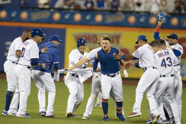 New York Mets' J.D. Davis reacts, center, is congratulated by teammates after he drove in the winning run with a single during the 10th inning of the team's baseball game against the Cleveland Indians, Wednesday, Aug. 21, 2019, in New York. The Mets won 4-3. (AP Photo/Mary Altaffer)