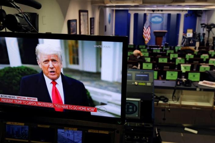 U.S. President Donald Trump is seen making remarks on a television monitor from the White House Briefing Room