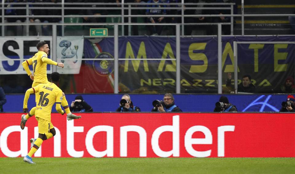 Barcelona's Carles Perez, top, celebrates with Barcelona's Moussa Wague after scoring his side's opening goal during the Champions League group F soccer match between Inter Milan and Barcelona at the San Siro stadium in Milan, Italy, Tuesday, Dec. 10, 2019. (AP Photo/Antonio Calanni)
