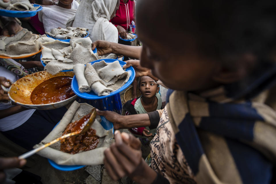 A young boy looks up as displaced Tigrayans line up to receive food donated by local residents at a reception center for the internally displaced in Mekele, in the Tigray region of northern Ethiopia, on Sunday, May 9, 2021. The 15 kilograms of wheat, half a kilogram of peas and some cooking oil per person, to last a month — was earmarked only for the most vulnerable. That included pregnant mothers and elderly people. (AP Photo/Ben Curtis)