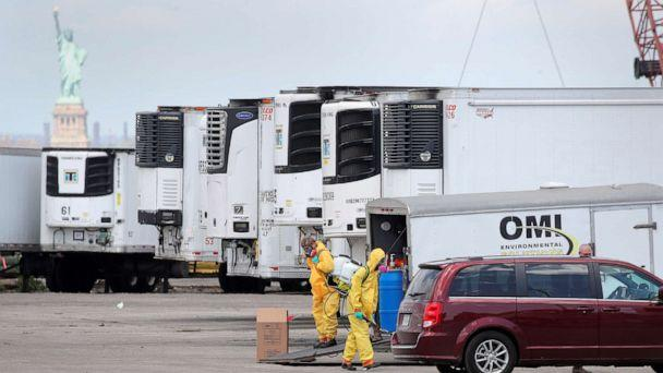 PHOTO: Workers are seen next to refrigerated tractor trailers used as a temporary morgue during the outbreak of the coronavirus disease (COVID-19) in the Brooklyn borough of New York City, May 4, 2020. (Brendan McDermid/Reuters)