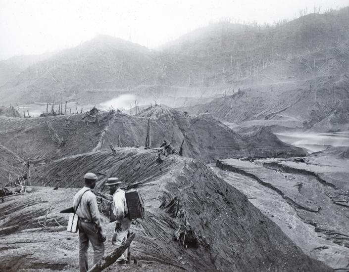 In this 1902 photo provided by York Museums Trust, men survey the devastation of the landscape following eruptions of La Soufrière, a volcano on the island of St. Vincent in the Caribbean. On April 9, 2021, La Soufriere once again started spewing hot torrents of gas, ash and rock, forcing thousands to evacuate to government-run shelters and private homes. (Tempest Anderson/York Museums Trust via AP)