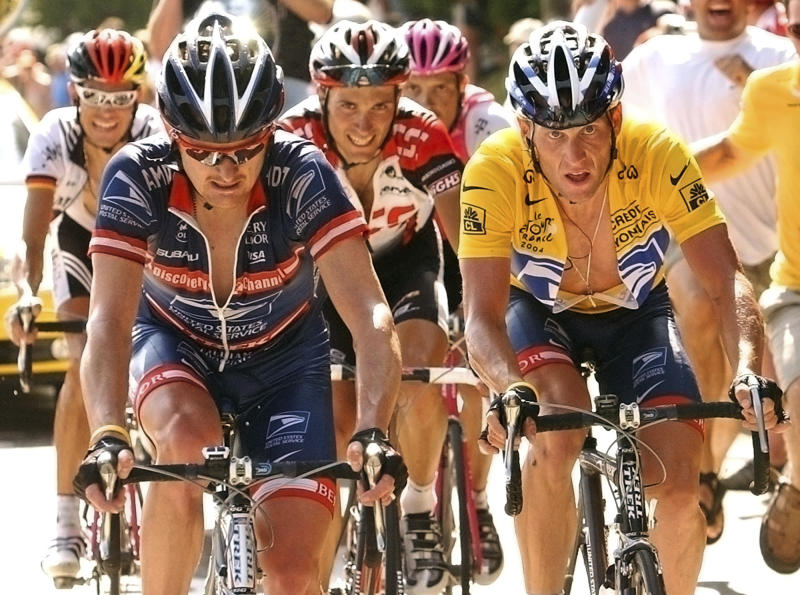 FILE - In this July 24, 2004, file pool photo, overall leader Lance Armstrong, right, of Austin, Texas, follows compatriot and teammate Floyd Landis, left, in the ascent of the La Croix Fry pass during the 17th stage of the Tour de France cycling race between Bourg-d'Oisans and Le Grand Bornand, French Alps. Landis is using money he earned by taking down Lance Armstrong to start his own cycling team. The man whose own doping saga cost him the 2006 Tour de France title and eventually helped expose Armstrong's cheating says he's building a developmental team for 2019 that will be based out of Canada. (Bernard Papon/L'Equipe via AP Pool, File)