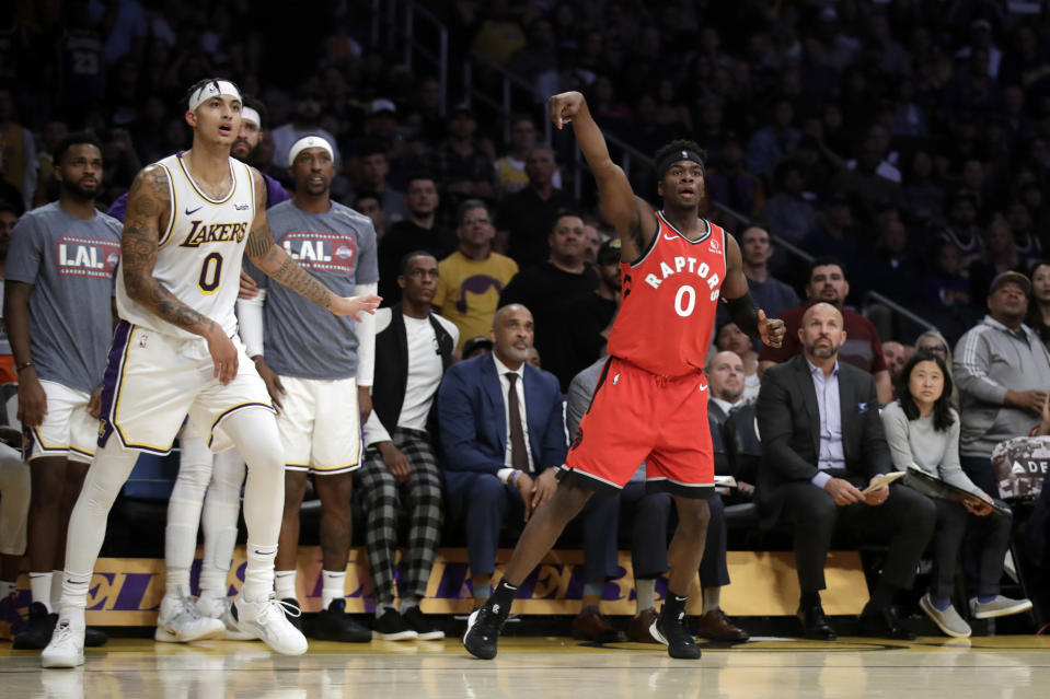 Toronto Raptors' Terence Davis follows through as he makes a 3-point basket next to Los Angeles Lakers' Kyle Kuzma (0) during the second half of an NBA basketball game Sunday, Nov. 10, 2019, in Los Angeles. (AP Photo/Marcio Jose Sanchez)