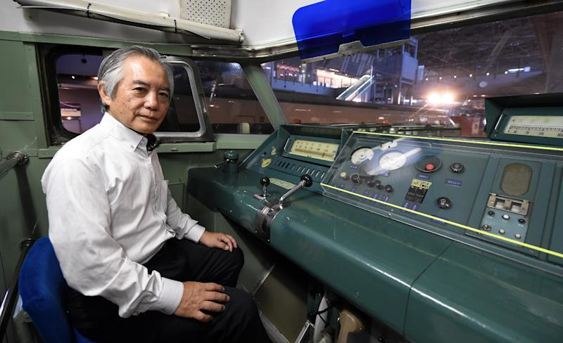 Former train conductor and current deputy director of the railway museum, Fumihiro Araki, poses for a photo inside the cab of Japan's first bullet train, at the museum in Omiya, Saitama prefecture, on August 1, 2014 (AFP Photo/Toshifumi Kitamura)