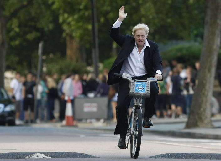 FILE - In this Friday, July 30, 2010 file photo Boris Johnson Mayor of London waves to the media as he helps launch a new cycle hire scheme in London. (AP Photo/Alastair Grant, File)