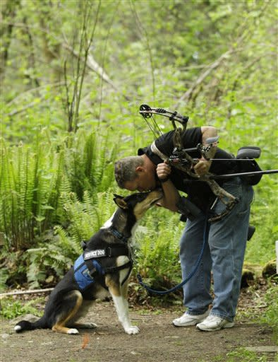 U.S. Army Spc. Mike Ballard kisses Apollo, his service dog, during a break in an archery shooting session, Friday, May 17, 2012, in Puyallup, Wash. Ballard says his dog helps him get through the worst symptoms of the post-traumatic stress disorder that is a remnant of an explosion in Afghanistan that ended his career as an Army medic. (AP Photo/Ted S. Warren)