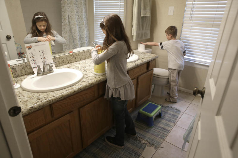 In this Saturday, Feb. 8, 2014 photo, Lily Cherry, 8, cleans her bathroom as her brother Aiden, 6, right, puts out a new roll of toilet paper at their home in Kingwood, Texas. Their mother Andrea Cherry has passed on her childhood practice of doing chores to her children believing it gives them a sense of family responsibility. For Cherry who works full time, having the kids help makes it possible for her and her husband who would otherwise do all the cleaning, to have enough time to take the kids to their soccer practices and games. (AP Photo/Pat Sullivan)