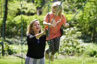 Holly Christensen, left, pushes her daughter, Lyra, on a swing, Thursday, May 13, 2021, in Akron, Ohio. Anti-abortion activists say 2021 has been a breakthrough year for legislation in several states seeking to prohibit abortions based on a prenatal diagnosis of Down syndrome. Opponents of the bills, including some parents with children who have Down syndrome like Holly, argue that elected officials should not be meddling with a woman's deeply personal decision on whether to carry a pregnancy to term after a Down syndrome diagnosis. (AP Photo/Tony Dejak)