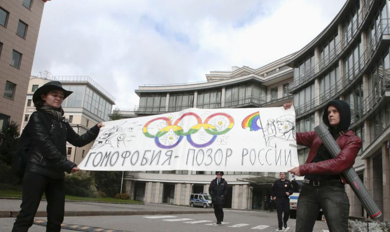 """Gay rights activists hold a banner as they protest against a ban on staging a gay pride parade during the Sochi 2014 Winter Olympic Games, in front of the Sochi 2014 organizing committee building in Moscow, September 25, 2013. The banner reads """"Homophobia is the shame of Russia"""". REUTERS/Tatyana Makeyeva (RUSSIA - Tags: SOCIETY CIVIL UNREST OLYMPICS SPORT)"""