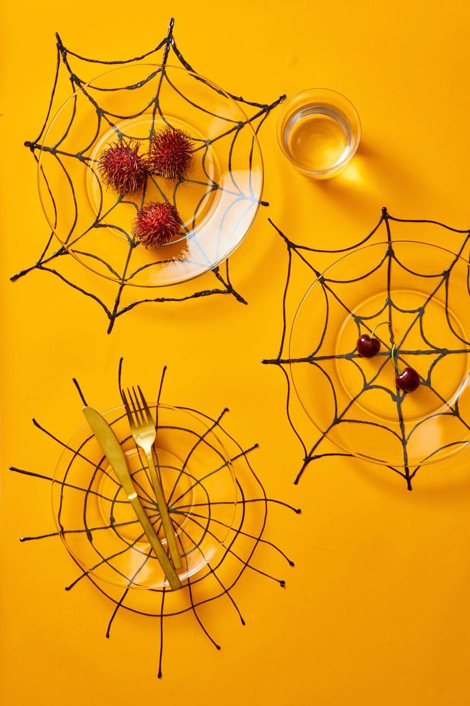 <p>Decorate the table with DIY placemats made out of puff paint and parchment paper. Using the puff pant, make a web shape onto the parchment paper. Let it dry and set overnight, so you can peel the paper off the back. Place it underneath a clear plate to show off your handwork. </p>