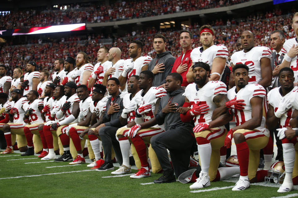 The San Francisco 49ers kneel and stand in solidarity on the sideline, during the anthem, prior to the game against the Arizona Cardinals at the University of Phoenix Stadium on October 1, 2017 in Phoenix, Arizona. The Cardinals defeated the 49ers 18-15. (Photo by Michael Zagaris/San Francisco 49ers/Getty Images)